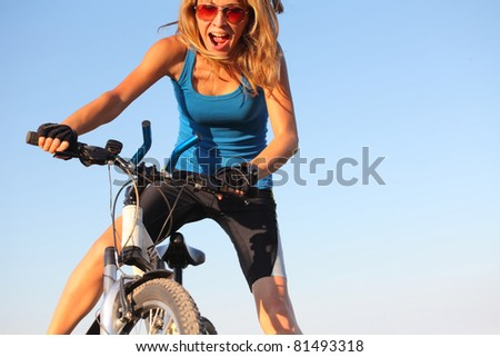 Young woman holding handlebar of a bicycle and shouting