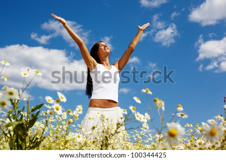 Young woman holding hands high up while enjoying the warm sunny day