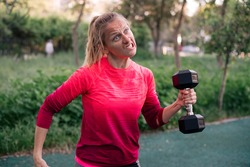 Young woman holding heavy dumbbell in one hand with very weird face, contorted in strange smile. Concept healthy and activity life, do exercise and spor toutdoor. place in park, green background.