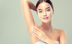 Young woman holding her arms up and showing underarms, armpit smooth clear skin .Girl showing clean armpit .Beauty portrait.Epilation and depilation of hair .