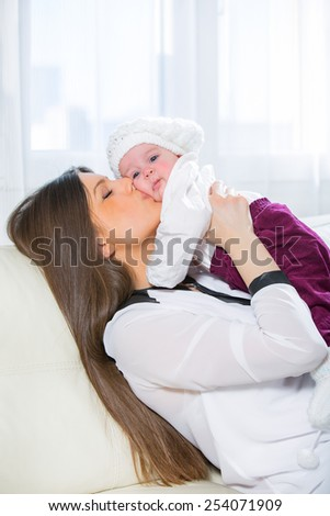 Young woman holding her baby in her arms while sitting on a sofa in the living room