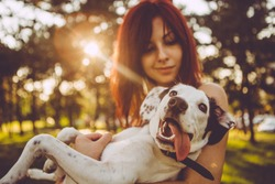 Young woman holding her dog in nature