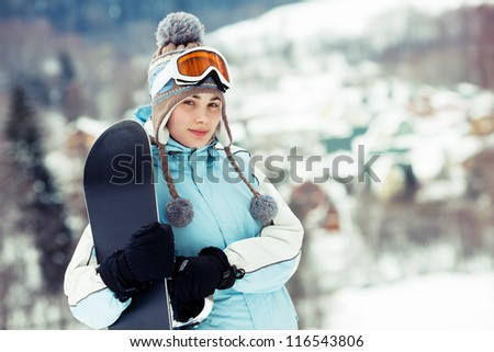 Young woman holding her snowboard, she's looking at camera and smiling, mountain village on background; copy space, close up