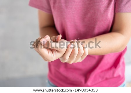 Young woman holding her wrist pain because using computer long time. De Quervain's tenosynovitis, Intersection Symptom, Carpal Tunnel Syndrome or Office syndrome.Disease and healthcare concept Foto stock ©