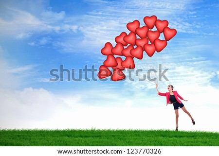 Young woman holding many red heart shape balloons on a green field