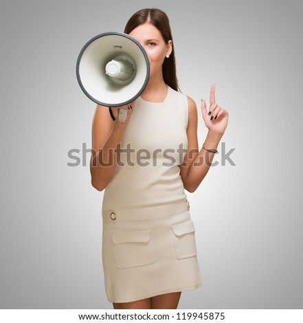 Young Woman Holding Megaphone against a grey background