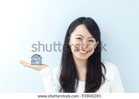 young woman holding model house