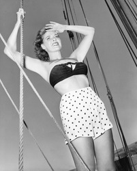 Young woman holding onto the ropes of an sail ship