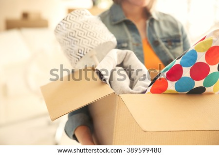 Young woman holding open cardboard box with things for moving into new house #389599480