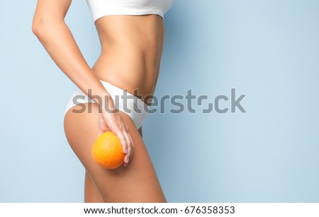 Young woman holding orange on light background. Cellulite problem concept Foto stock ©