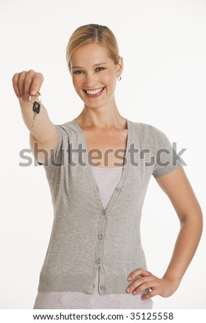young woman holding out keys towards camera on white seamless background