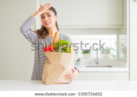 Young woman holding paper bag full of groceries stressed with hand on head, shocked with shame and surprise face, angry and frustrated. Fear and upset for mistake.
