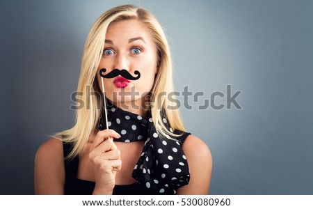Young woman holding paper party sticks on a gray background #530080960