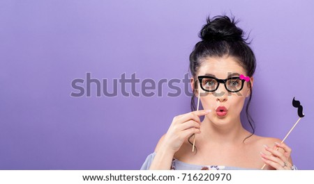 Young woman holding paper party sticks on a solid background #716220970