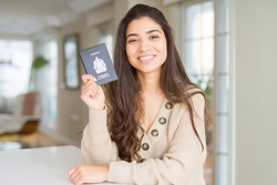Young woman holding passport of Canada with a happy face standing and smiling with a confident smile showing teeth