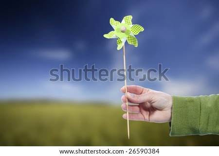 Young woman holding pinwheel windmill outdoors - spring concept