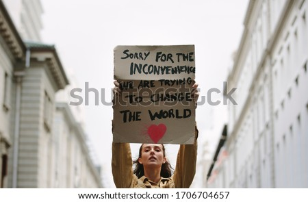 Young woman holding poster and protesting. Demonstrator making protest about climate change. Stok fotoğraf ©