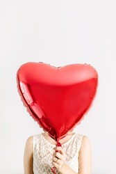 Young woman holding red heart shape balloon.