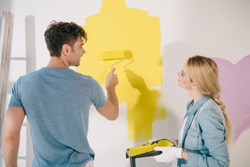 young woman holding roller tray while boyfriend painting wall in yellow with paint roller