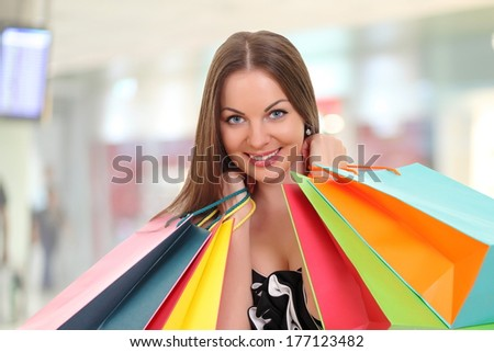 young woman holding shopping bags and smiling at camera
