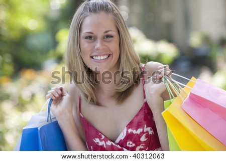 Young woman holding shopping bags and smiling at the camera. Horizontal format.