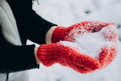 Young woman holding snow in her hands in red mittens, winter, fun, joy, sports, recreation, children. Valentine's Day