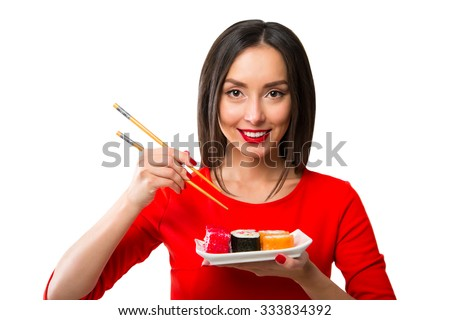 Young woman holding sushi with a chopsticks, isolated on white Foto d'archivio ©