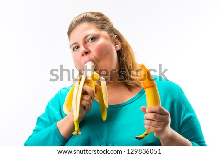 Young woman holding two bananas in hand, condom is pulled over one, eating another banana