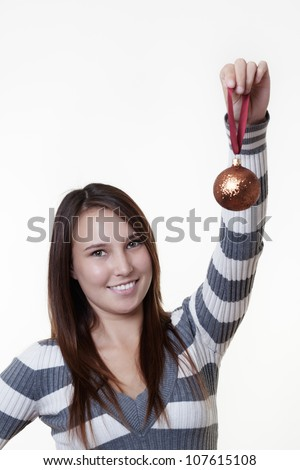 young woman holding up christmas baubles decorations about to hang on a tree - stock photo