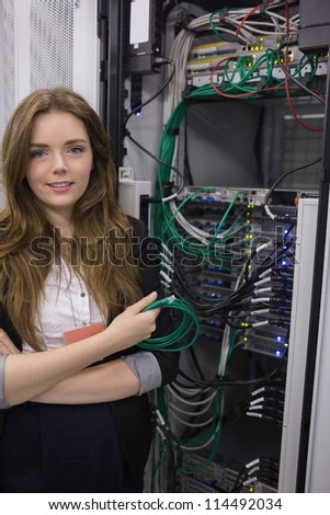 Young woman holding usb cable in front of rack mounted servers