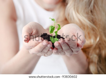 Young woman holding young plant in her hands. Shallow depth of field