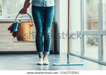Young Woman holds Bucket with Cleaning Equipment. Closeup of Beautifull Girl wearing Gloves holding Bucket with Cleaning Supplies ready to start Cleaning Apartment. Woman preparing to Clean