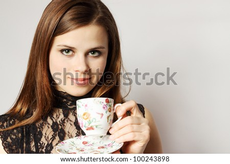Young woman holds cup with the tea