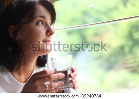 young woman holds glass and looks in train`s window