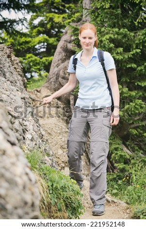 Young woman holds on to a metal cable support as she navigates a narrow Alpine hiking trail.