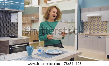 Young woman housewife choosing kitchen furniture to buy in store. Happy pretty girl excited about low prices in showroom buying built-in kitchen garniture Stok fotoğraf ©