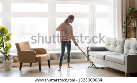 Young woman housewife clean wash hardwood floor in modern living room interior, tidy girl cleaner maid holding mop at home, housekeeping and household, domestic housework cleaning service concept