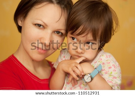 Young woman hugging a little pensive girl