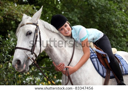 Young woman hugging her horse