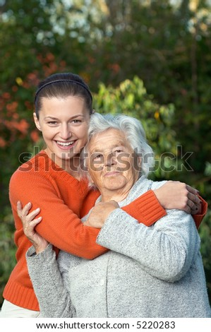 Young woman hugging her ninety year old grandmother