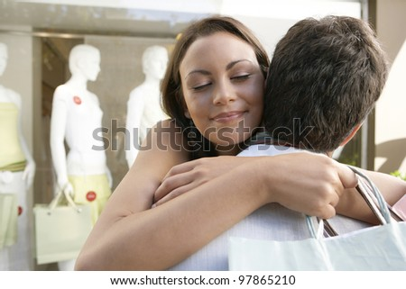 Young woman hugging man outside a fashion store.