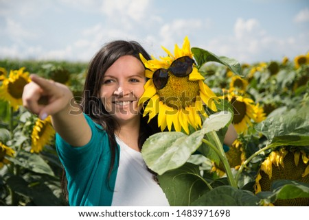 Young woman hugging sunflower at the field