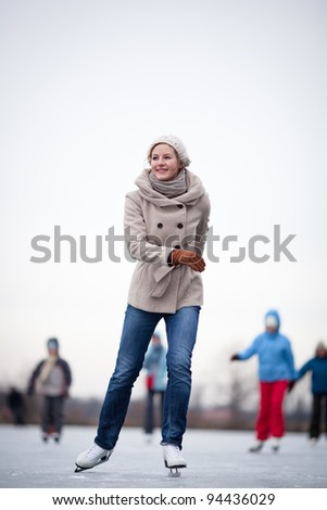 Young woman ice skating outdoors on a pond on a freezing winter day