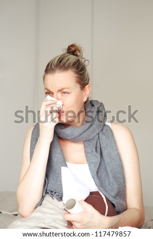 Young woman ill with seasonal chills and flu sitting in bed blowing her nose on a tissue with a scarf around her neck