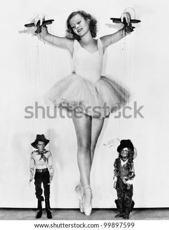 Young woman in a ballerina tutu keeps on her toes to control the men at her feet