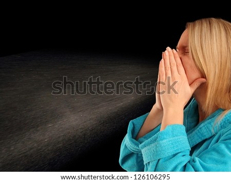 Young woman in a bath robe sneezing with back-light