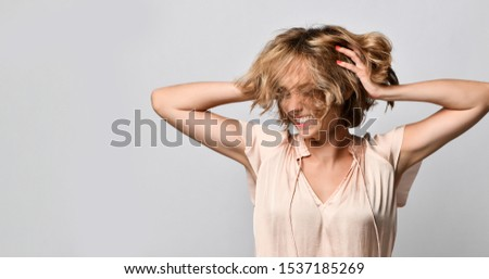 young woman in a beige satin blouse with short sleeves holds her head in her hands laughing. The concept of joy, happiness, joy, fun