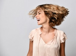 young woman in a beige short-sleeved satin blouse shakes her head with her hair. The concept of joy, happiness, joy, fun