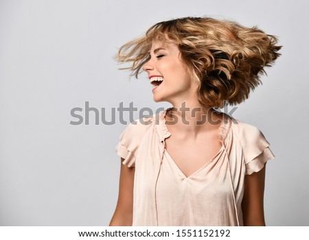young woman in a beige short-sleeved satin blouse shakes her head with her hair. The concept of joy, happiness, joy, fun #1551152192