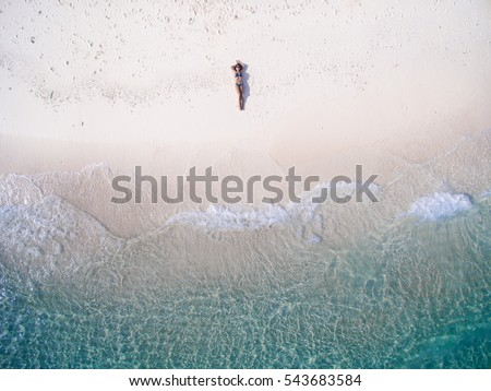 Young woman in a bikini lying on the back on the sand near the waves of blue sea. Top view. Kai island, Andaman Sea, Phuket, Thailand. Aerial Shooting. #543683584